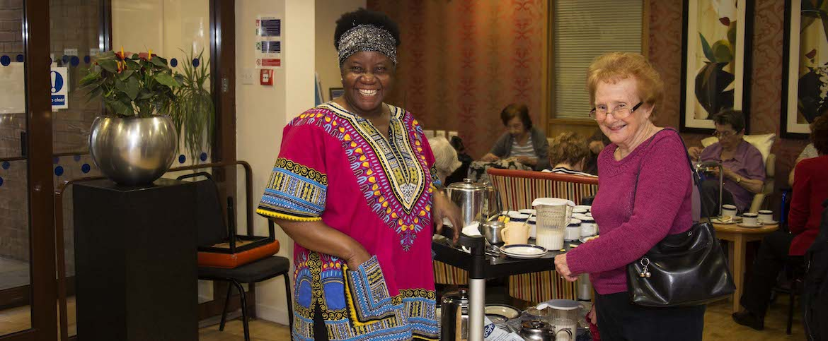 Two women stand in front of a tea trolley and smile.