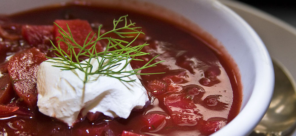 A bowl of borscht garnished with dill and a dollop of sour cream.