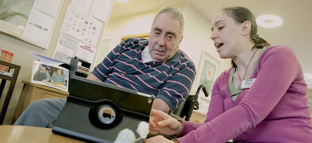 A middle aged man in a wheelchair watches as a younger woman demonstrates an iPad.