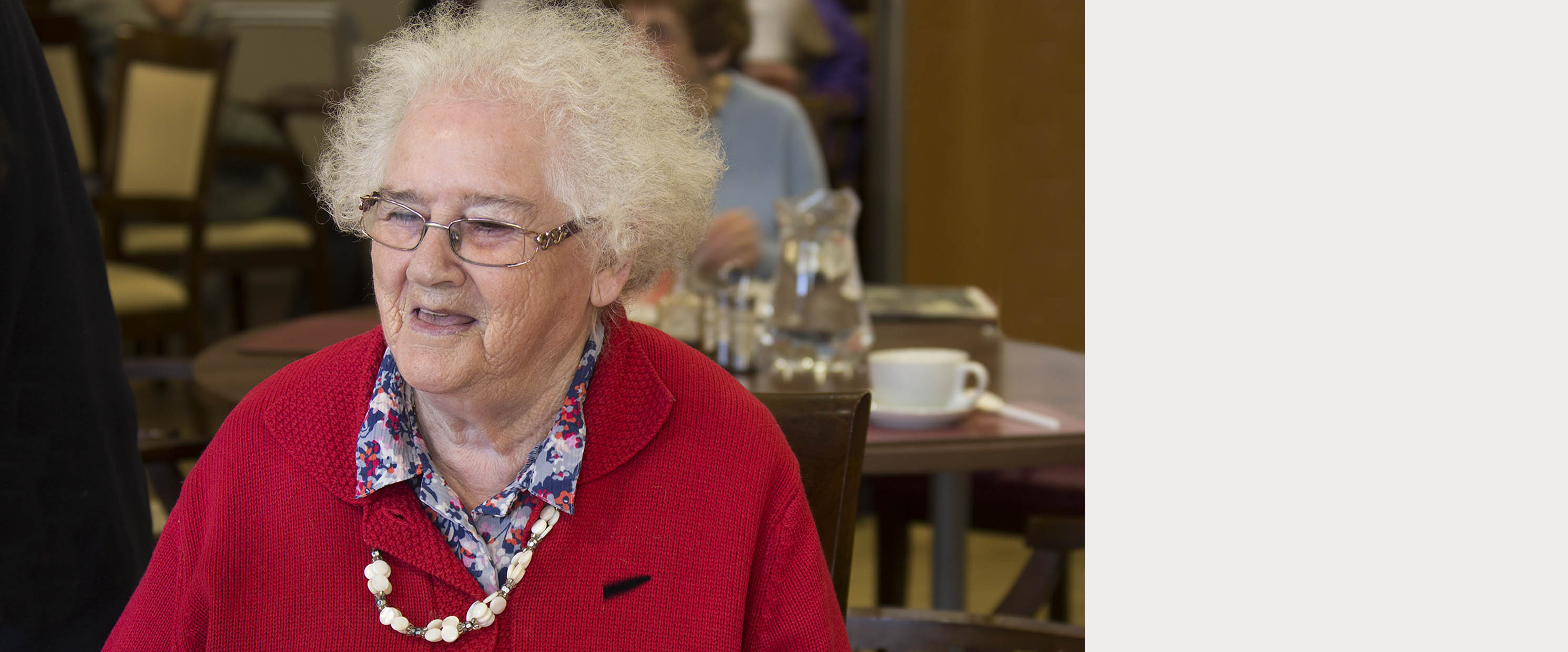 Older woman has a big smile on her face as she sits at a table in a community centre.