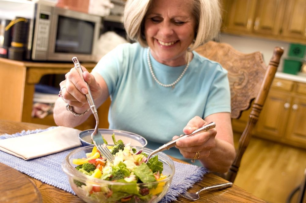 A happy woman dishes out a salad.