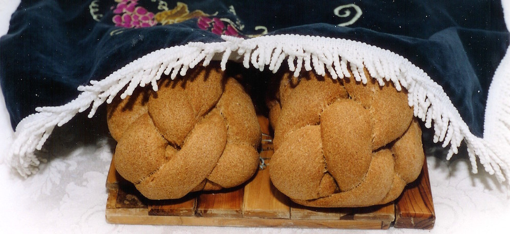 Photo of two homemade whole wheat challahs placed on a decorative olive-wood cutting board and covered by a traditional embroidered Shabbat challah cover.