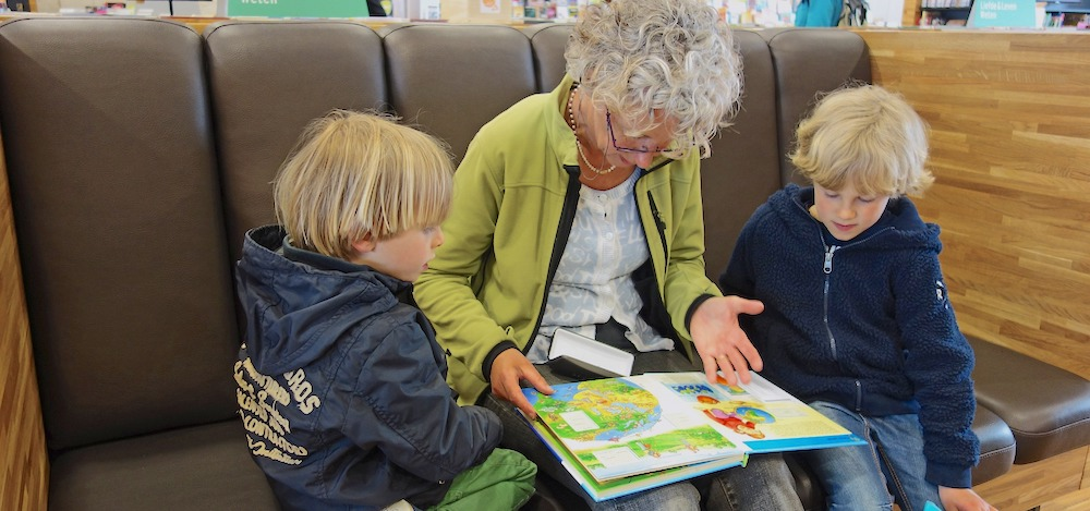 An older woman reads a book to two young children on either side of her.