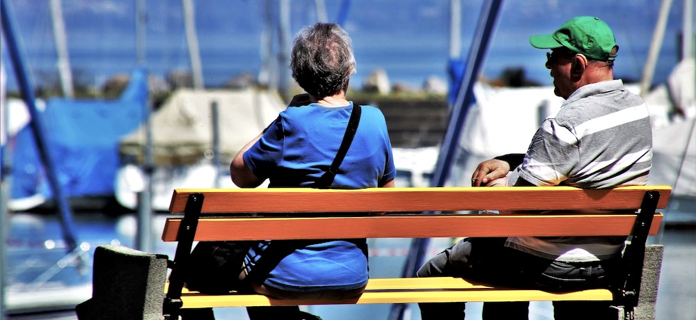 Two people with their backs to the camera—an older woman on the left and an older man on the right—sit side by side on a bench that looks over a marina.
