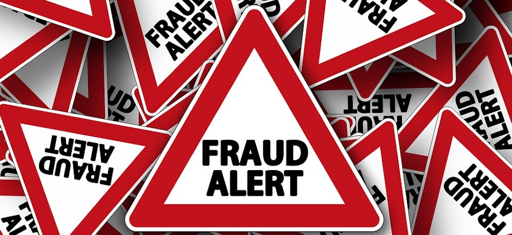 Red and white traffic traffic triangles are emblazoned with the word FRAUD, in black, and scattered in a pile..