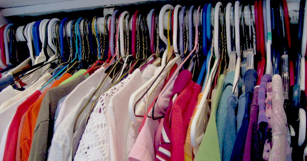 A closet is filled with multicolored short sleeve tops.