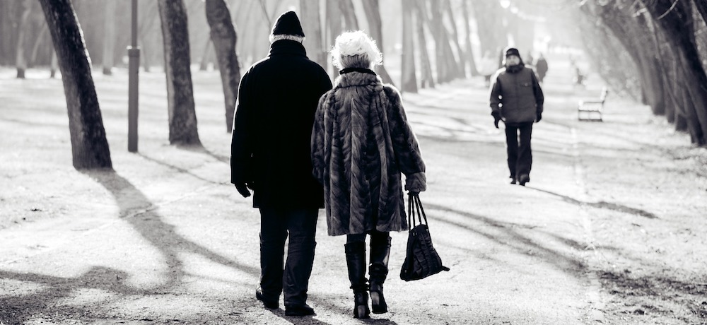 An older couple walks hand in hand down a tree lined path in winter.