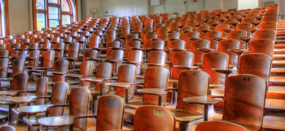 An older lecture hall is filled with empty wooden chairs.