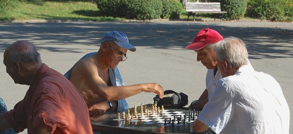 Three two older men sit outside playing chess while another man watches.