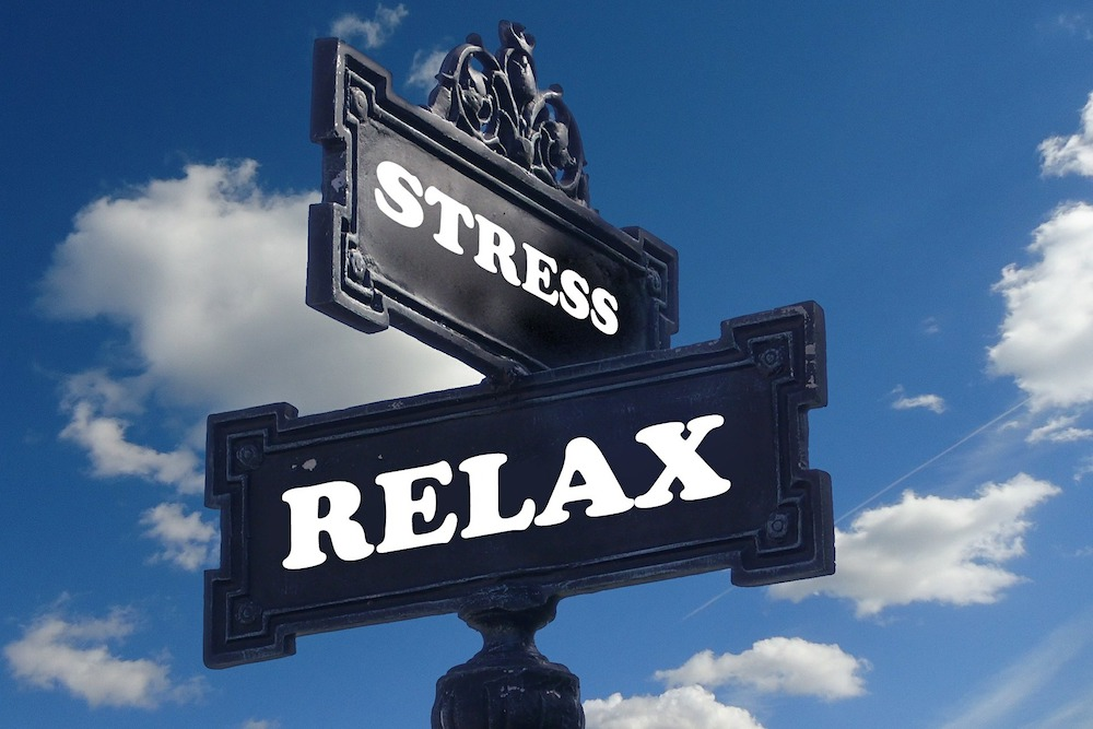 An old fashioned road sign has two placards, with the words stress and relax, pointing in different directions.