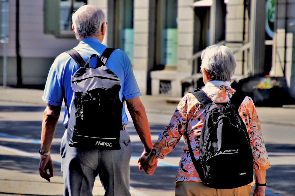 An older couple walk with their backs to the camera and carry backpacks as they stroll together in a sunny street.