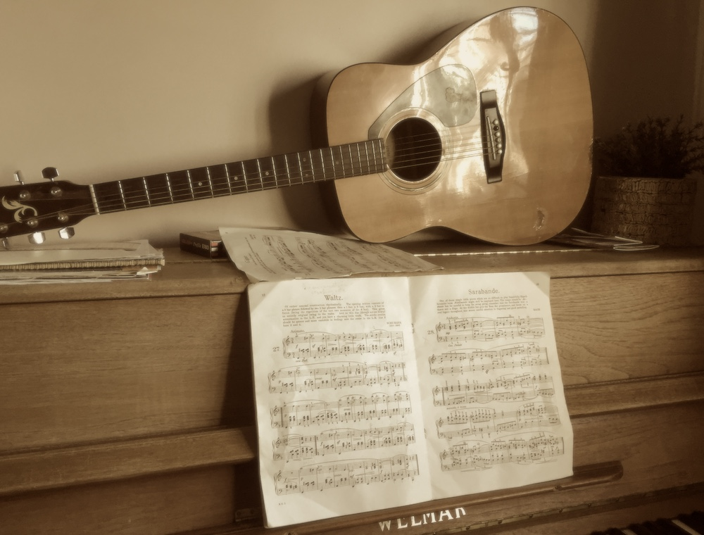 An acoustic guitar sits on top of a piano that has sheet music on the music holder.