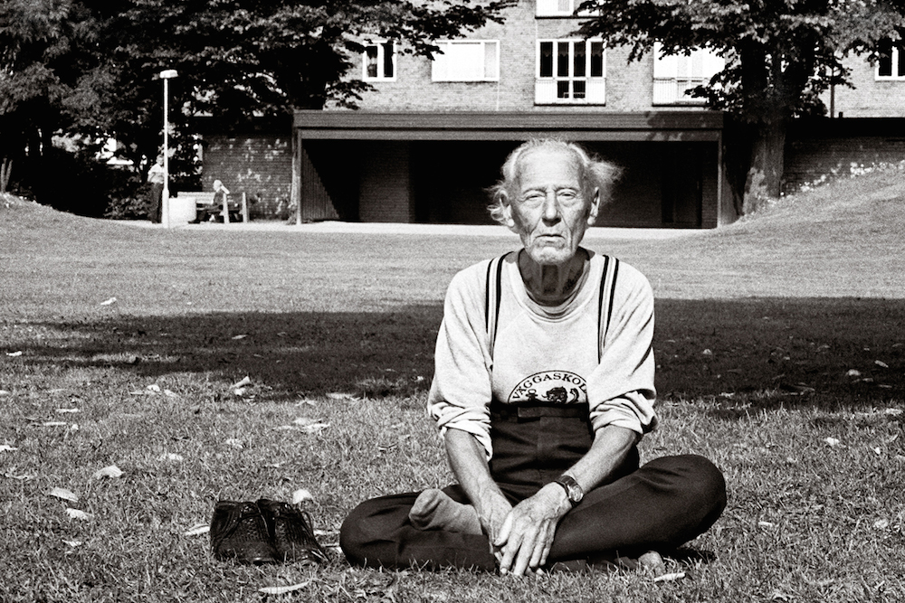 An older man sits on the grass cross legged as he clears his mind to meditate.