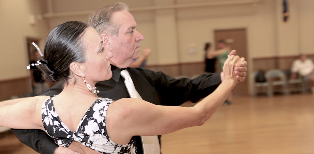 A middle aged couple strike a dramatic pose during a tango dance class.