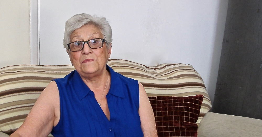 An older woman wearing glasses sits on a striped sofa.