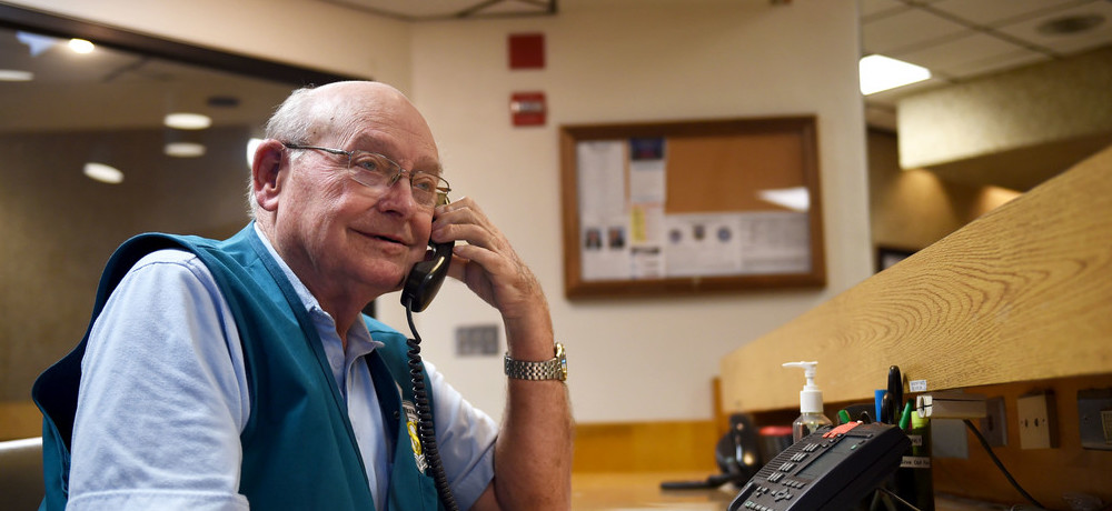 An older male volunteer answers the phone while manning the information desk at a hospital.