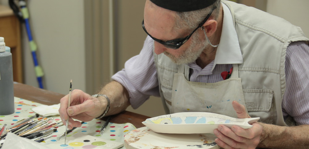 An older Jewish man paints a ceramic fish art project.