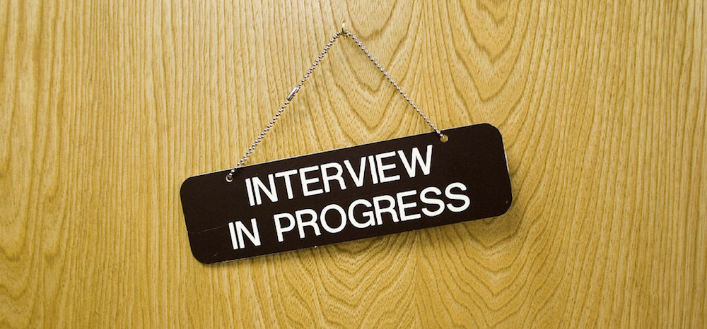 "An ""Interview in progress"" sign is hanging on wooden door."