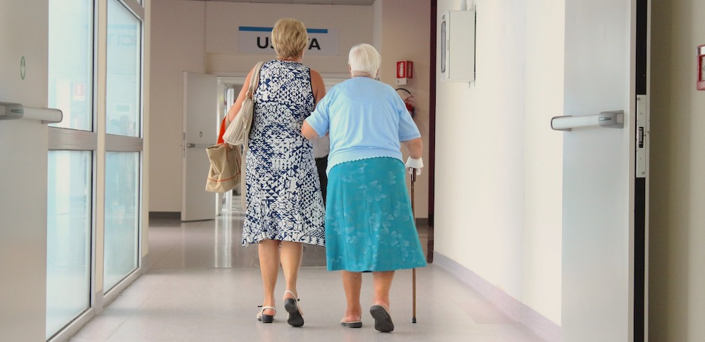 From the back we see an older woman with a hospital bracelet and cane walking arm in arm down a hospital corridor with a younger woman.