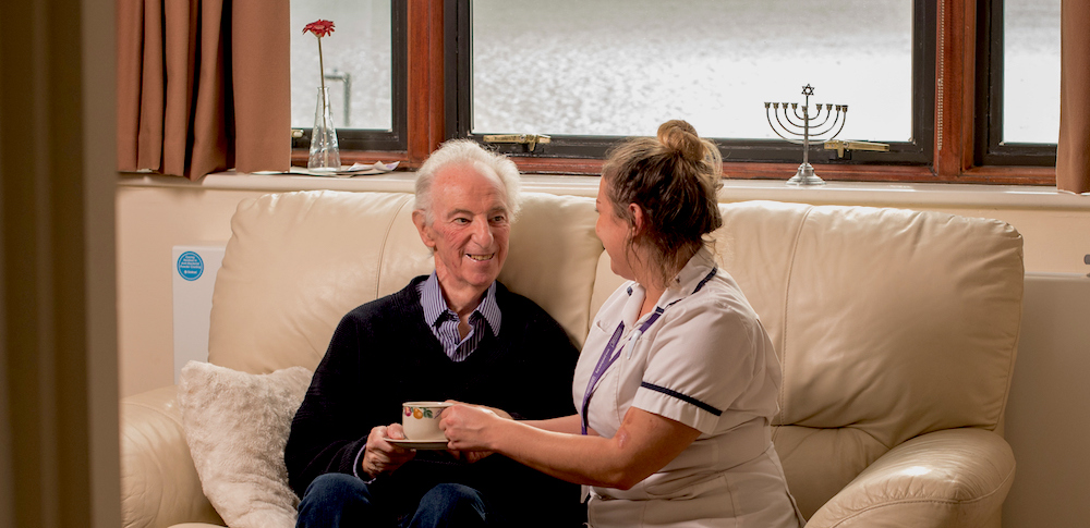 An older man sits on a sofa with a nurse who hands him a teacup.