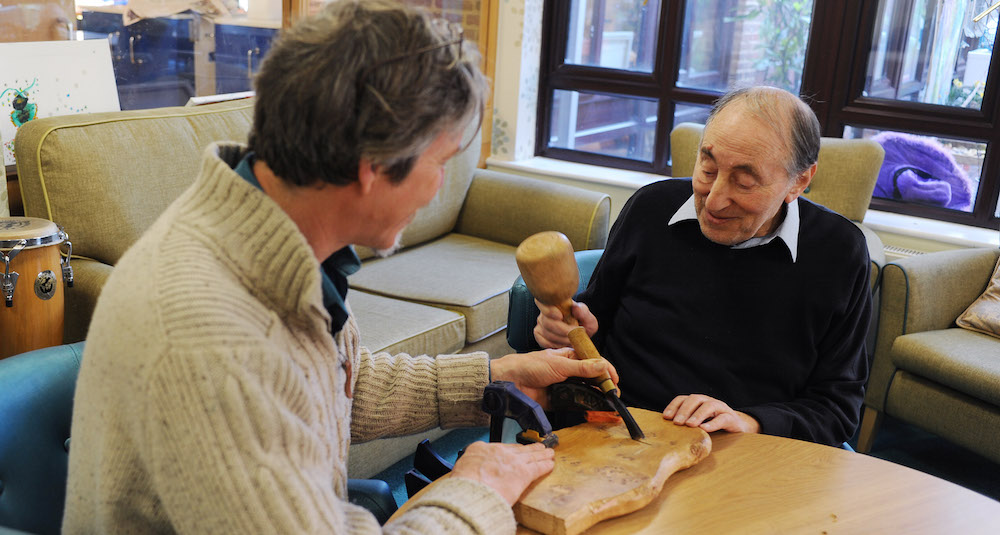 A middled aged man helps an older man with a woodworking project.