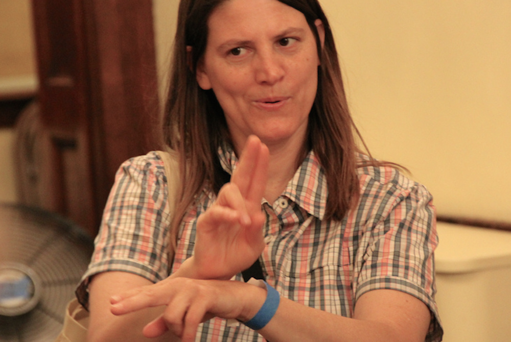 A woman uses sign language to communicate.