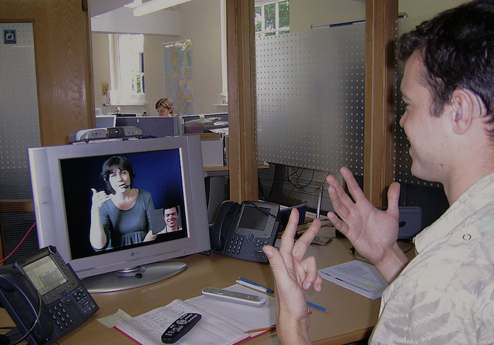 Hearing impaired person at his workplace communicates with a hearing person via a Video Relay Service video interpreter (shown on-screen), using a videophone