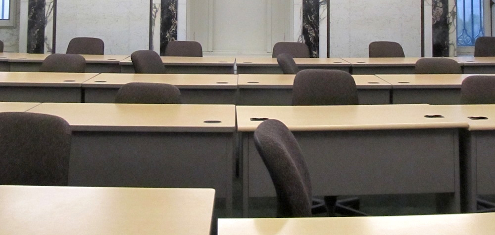 An empty university classroom with rows of desks and chairs.