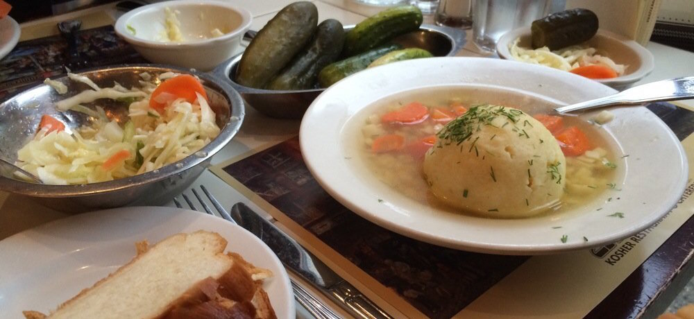 A bowl of matzoh ball soup is placed on a restaurant table where it is surrounded by pickles, cole slaw and challah bread.
