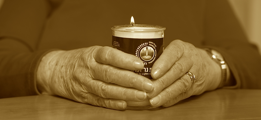 A woman puts her hands around a Jewish bereavement candle.