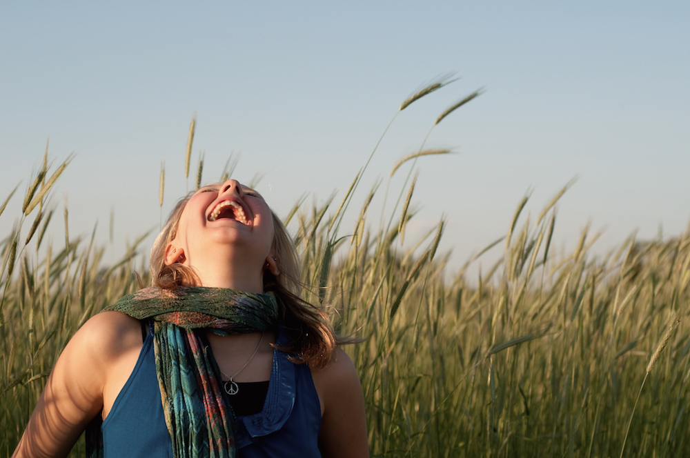 Woman throws her head upward and laughs in a field of grain.