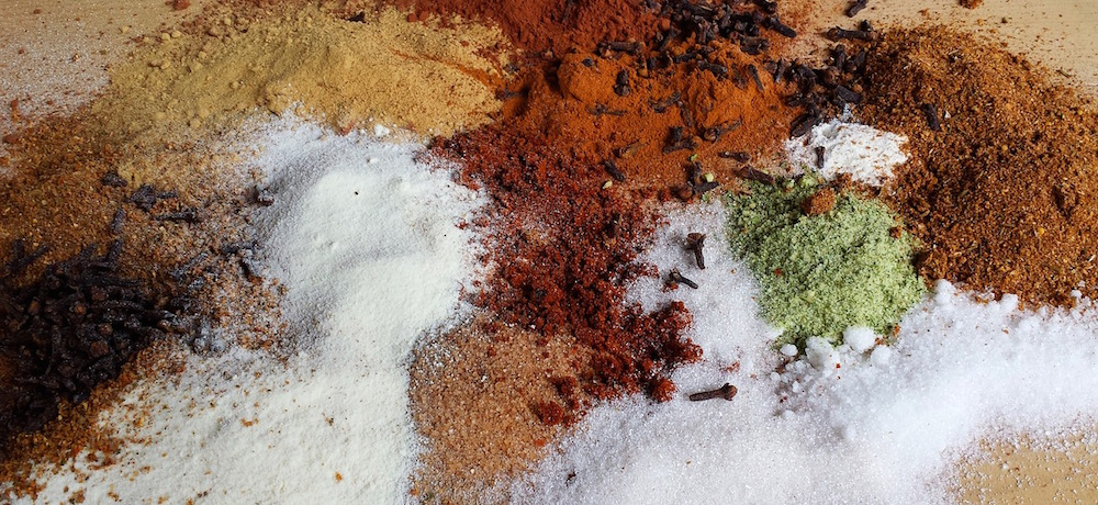 Small piles of salt, sugar, cloves, cinnamon, cumin and other spices spread on a table.