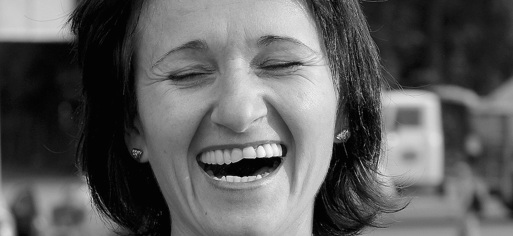 Woman laughs heartily with her mouth open and her eyes shut. (Photo: Pixabay.)