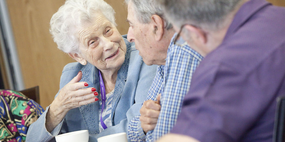 Woman chats with family members over tea.