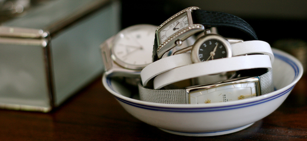 Wristwatches organised on top of a dresser.