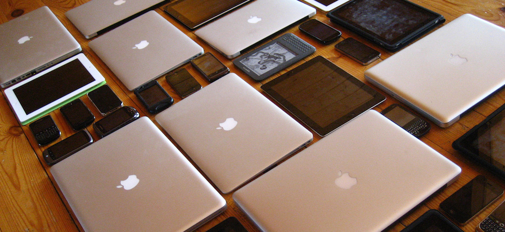 An array of Apple laptops, tablets and mobile telephones.