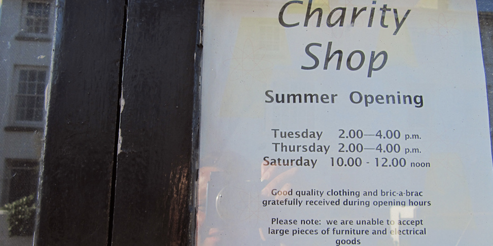 Charity shop sign with summer hours posted.