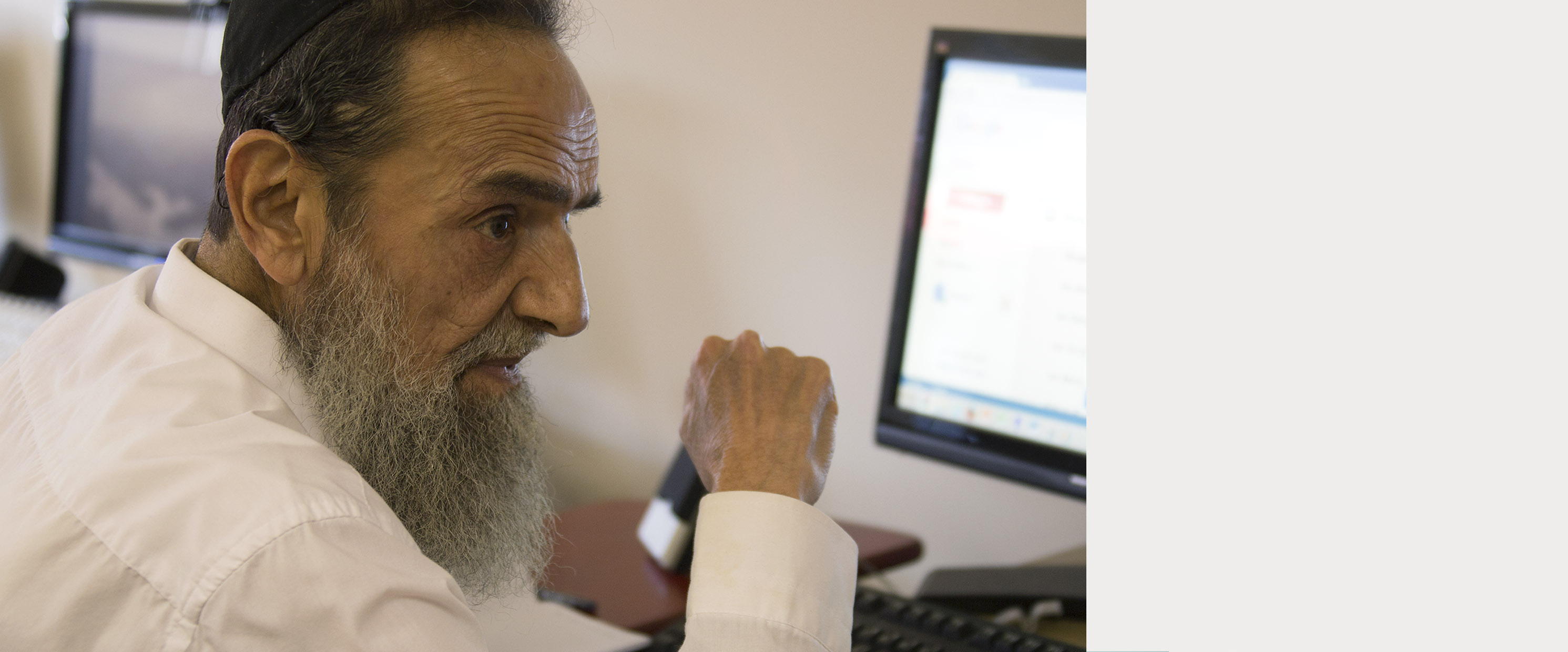 Older Jewish man in front of a computer
