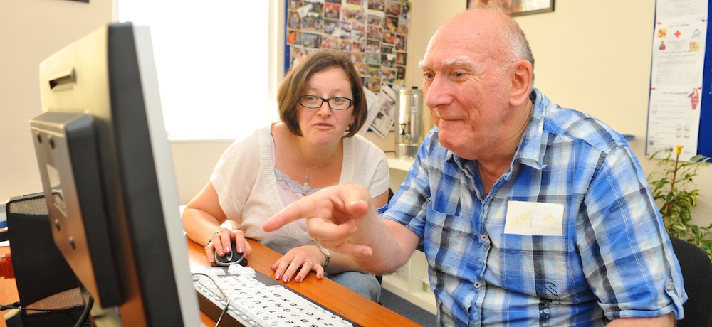 A woman shows an older man how to use a computer.