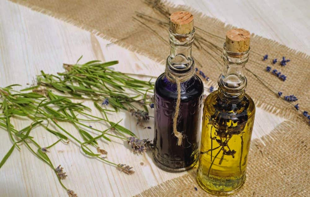 Two bottles of aromatherapy oils filled with lavender are side by side next to a fanned out display of fresh and dried lavender.