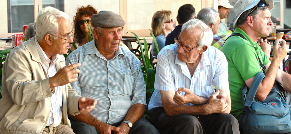Older men in discussion as they sit out on a bench in the sunshine.