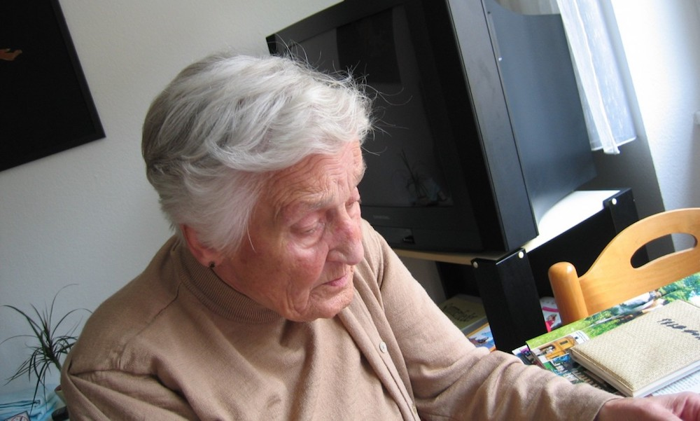 An older woman sits by herself and looks downward; a television and scrapbooks are in the background.