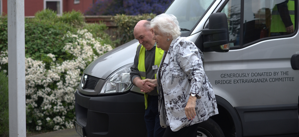 An older woman is assisted by a gentleman as she leaves a transport van.
