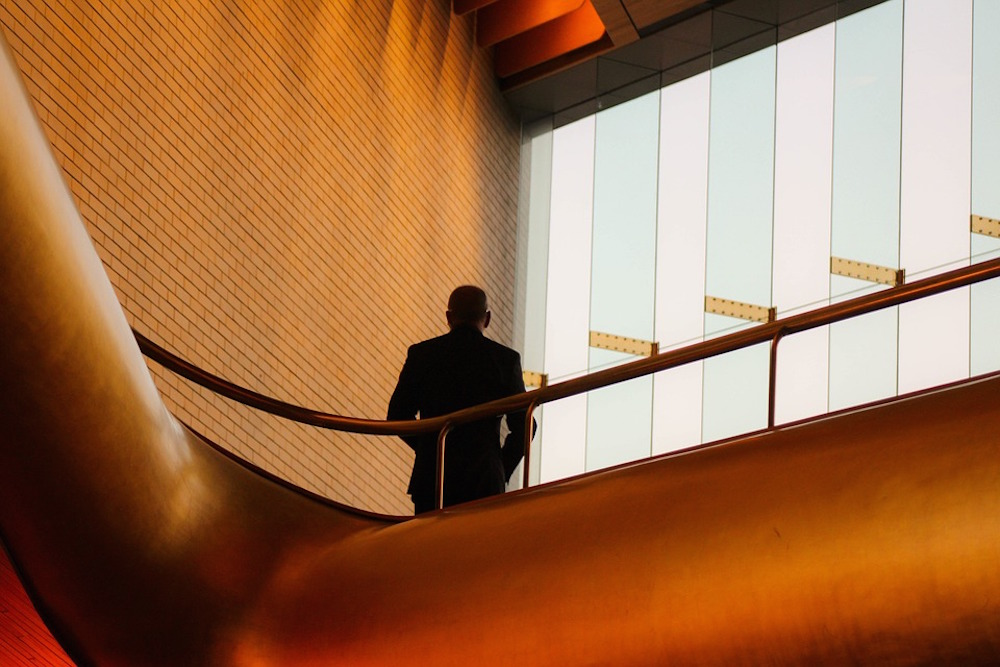 A solitary man stands in the atrium of an office.