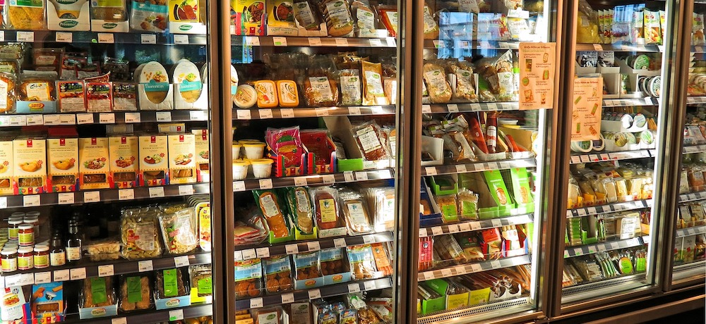 A refrigerated food case in a grocery store is filled with vegan, dairy and gluten free food alternatives.