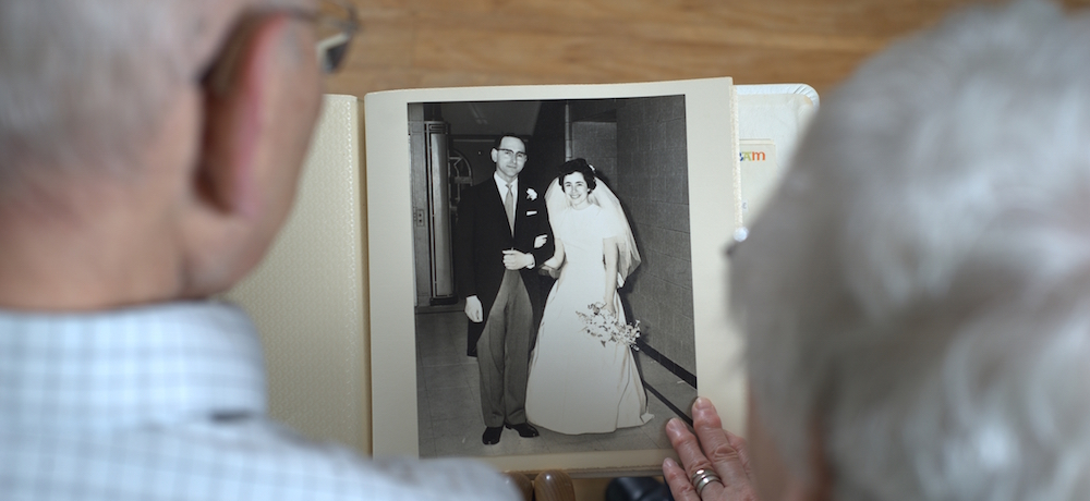 Older man and older woman reminisce over a black and white wedding photo album.