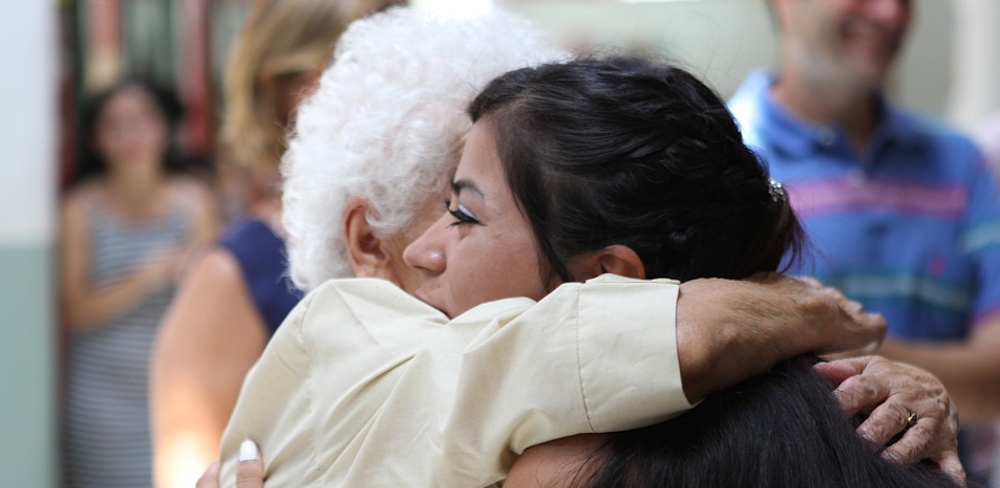 A happy grandmother hugs her younger relative.