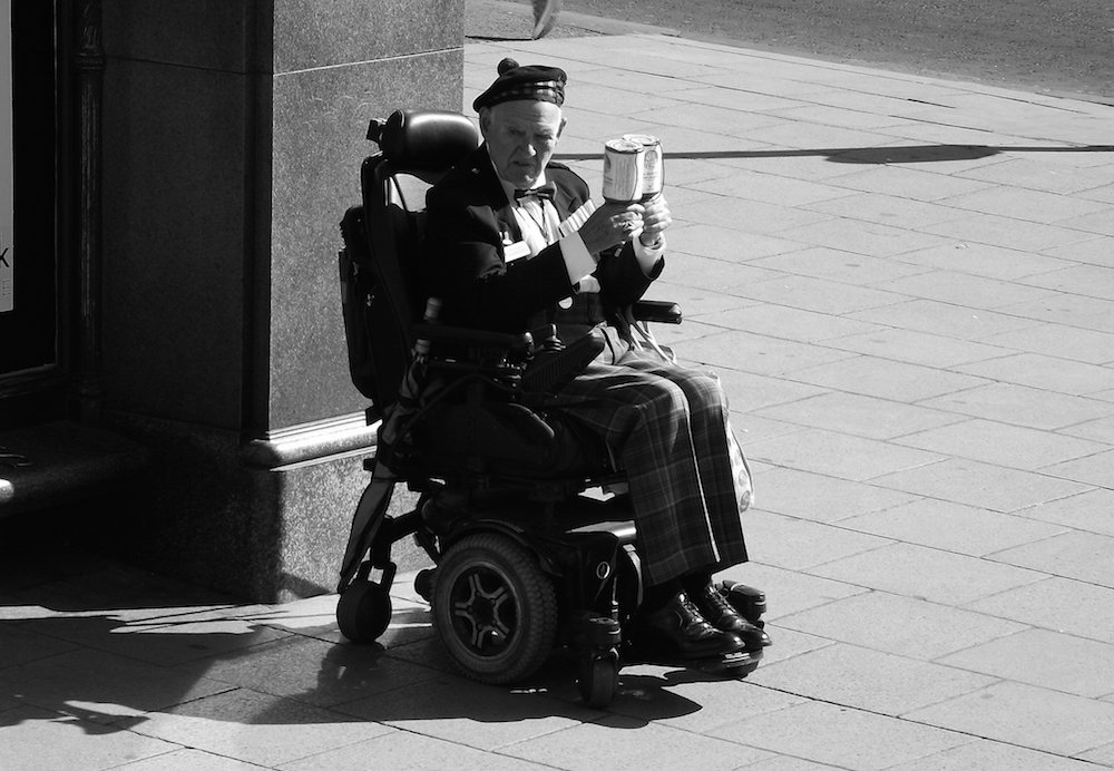 In his mid 90s, this veteran fundraiser sits in his wheelchair on the streets of Edinburgh.