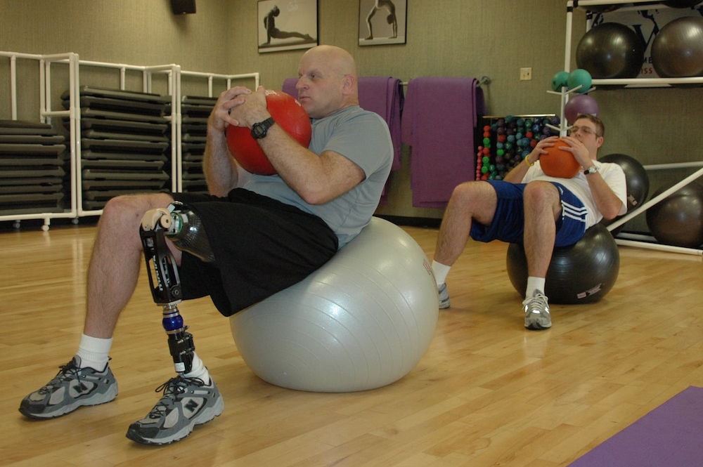 A man with an amputated leg uses a yoga ball to perform exercises in a gym.