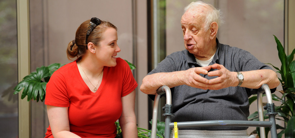 Young woman smiles as she sits next to an older man, who leans over a walking frame.